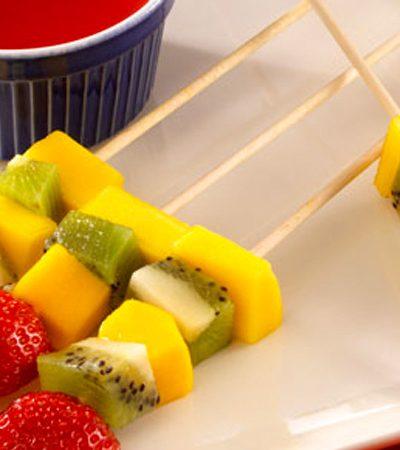 Banderillas de frutas frias bañadas en salsa de fresa