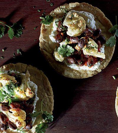 taquitos de coliflor rostizada y frijoles picantes con cilantro